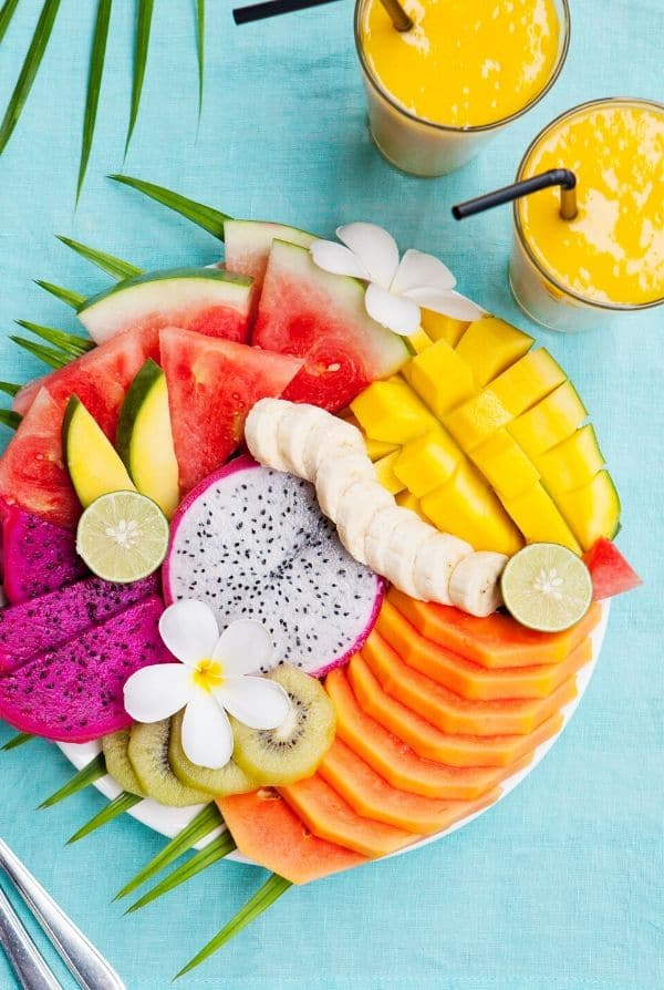 colorful platter of tropical fruit and smoothies