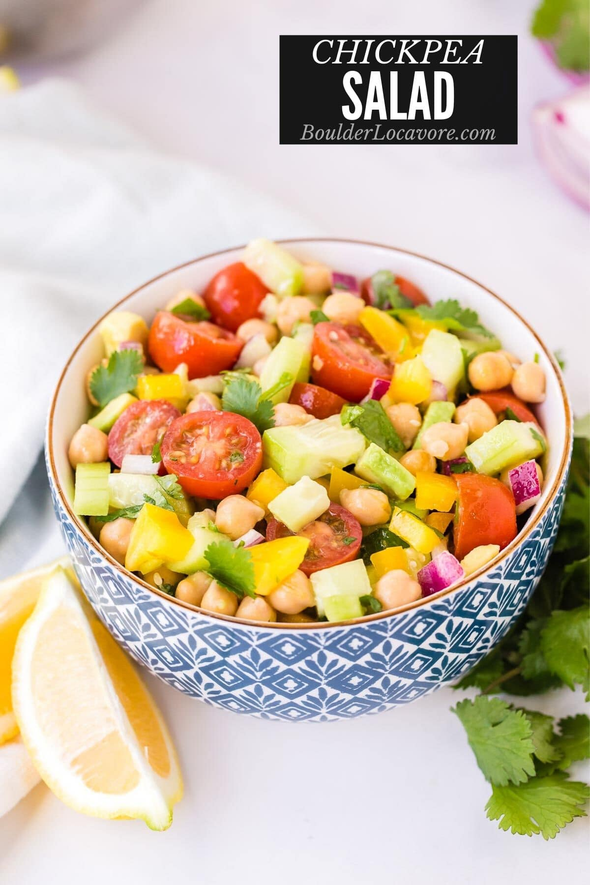 Chickpea Salad in a blue and white bowl with lemon wedges (title image)