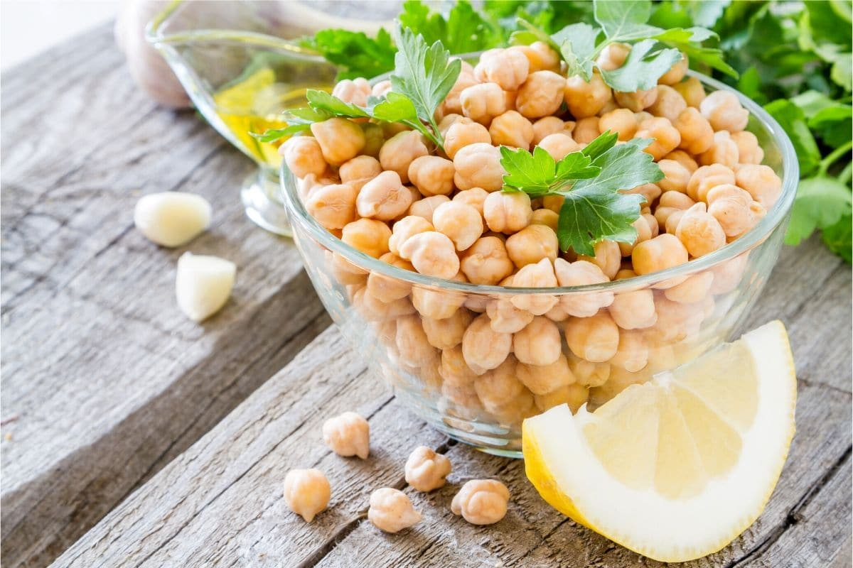 chickpeas in a bowl with lemon wedges