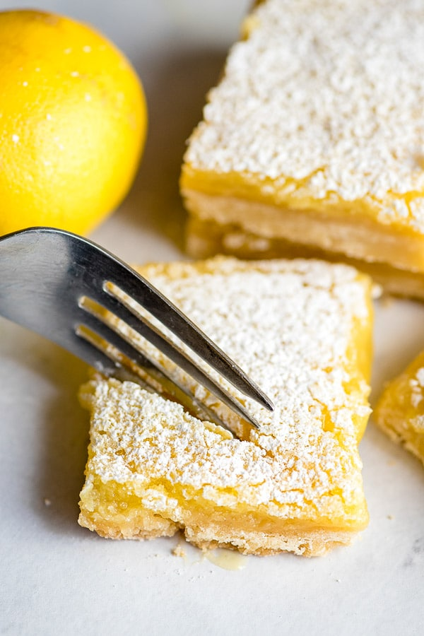 fork cutting into a lemon bar