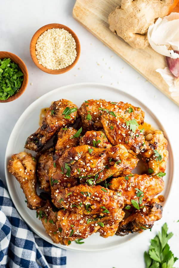 mound of sticky grilled chicken wings on a white plate