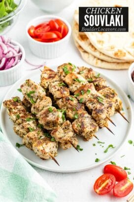 white plate of grilled Chicken Souvlaki skewers with flatbread and vegetables in the background