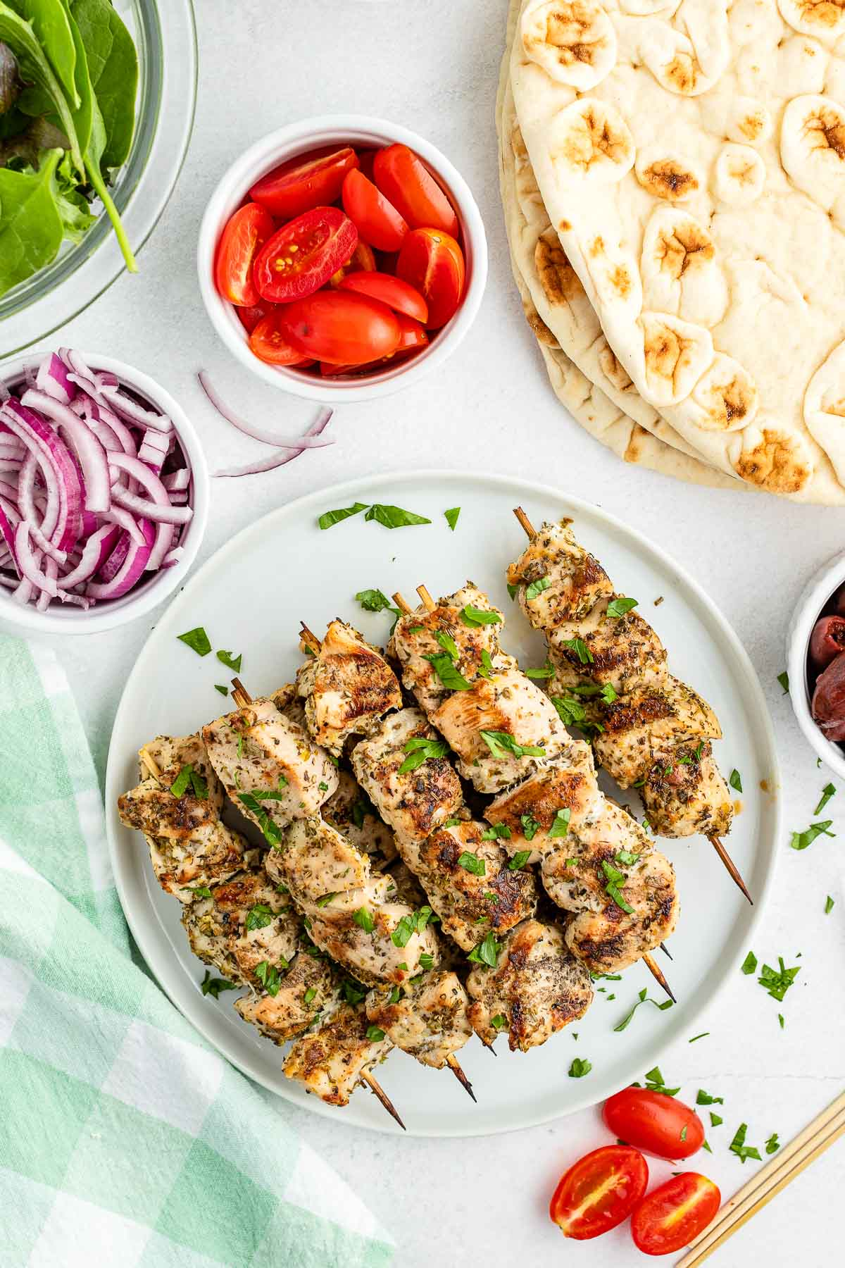 grilled chicken souvlaki skweres on a plate surrounded by containers of prepared vegetable and flatbread