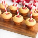 Mini Corn Dog Muffins with striped sticks on a wood cutting board