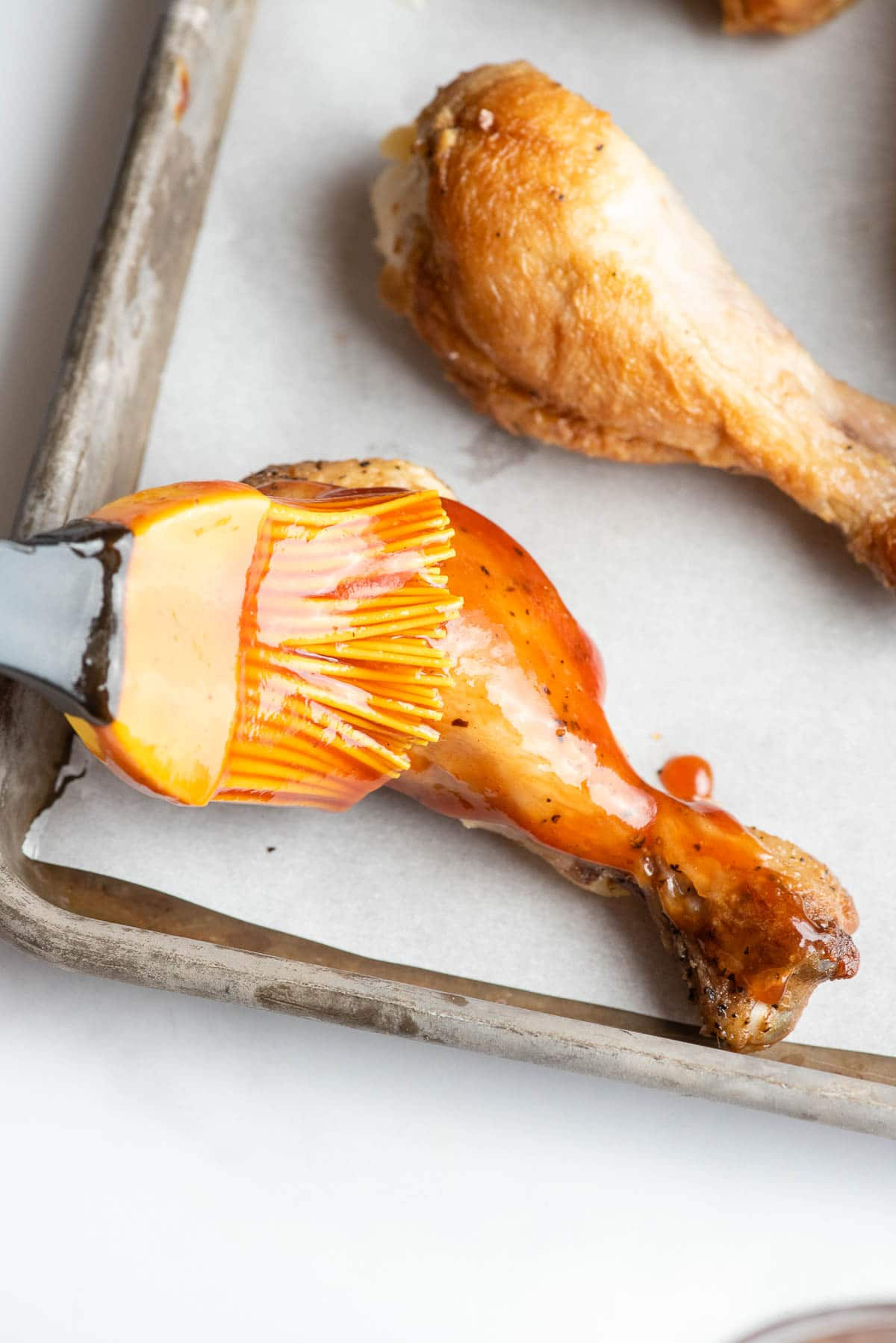brushing barbecue sauce on a chicken drumstick