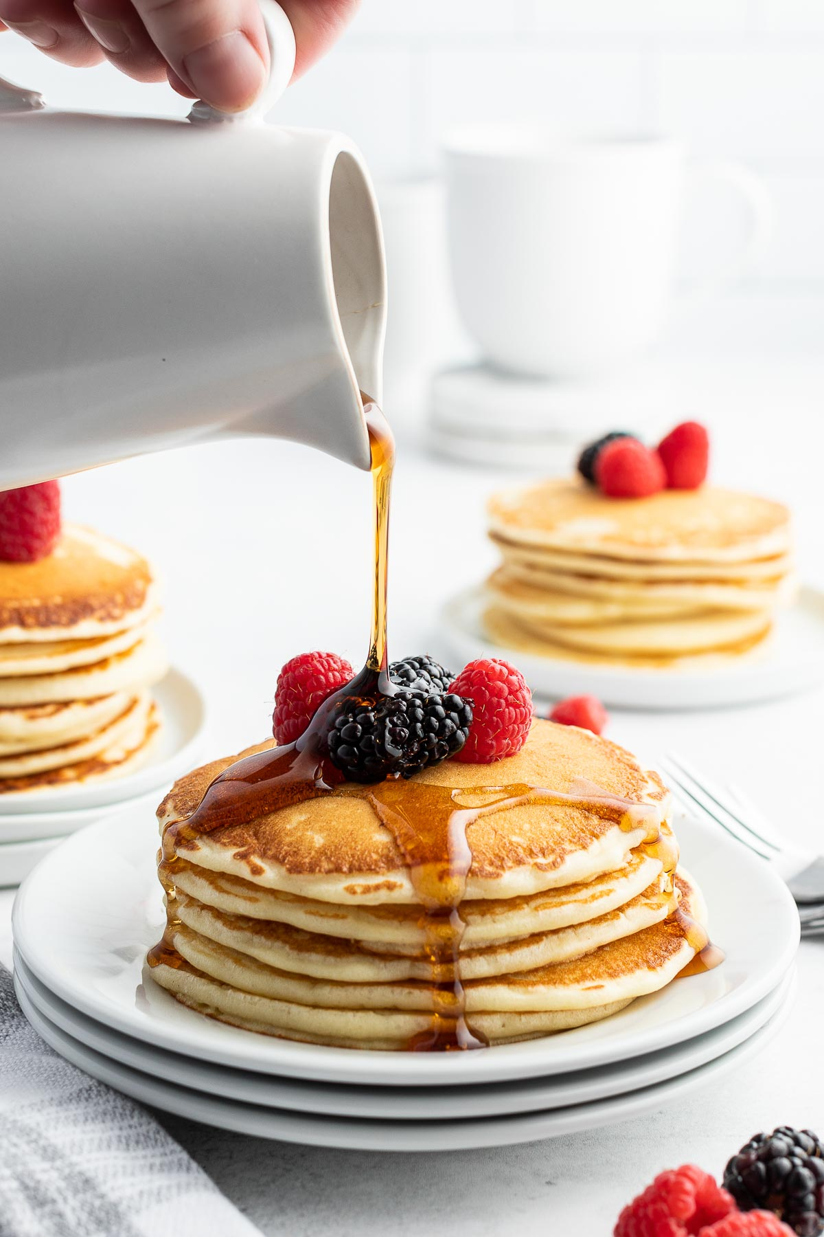 buttermilk pancakes syrup pouring on top from white pitcher