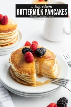 stack of fluffy buttermilk pancakes on a white plate with wedge cut out