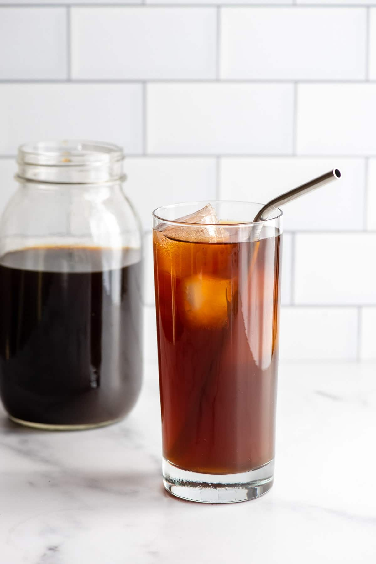 glass of cold brew coffee with ice and a metal straw and jar of coffee behind