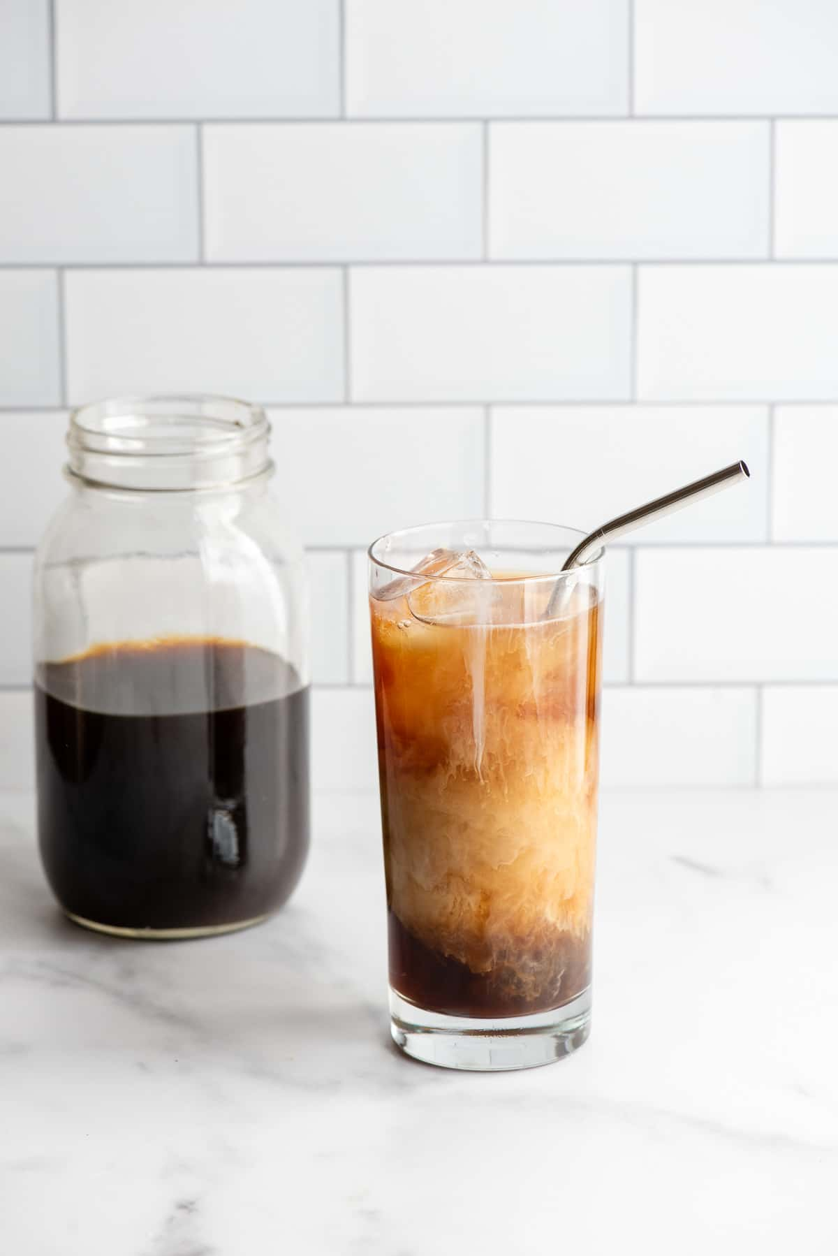 glass of cold brew coffee with cream and a metal straw with a jar of cold brew coffee in a jar in background