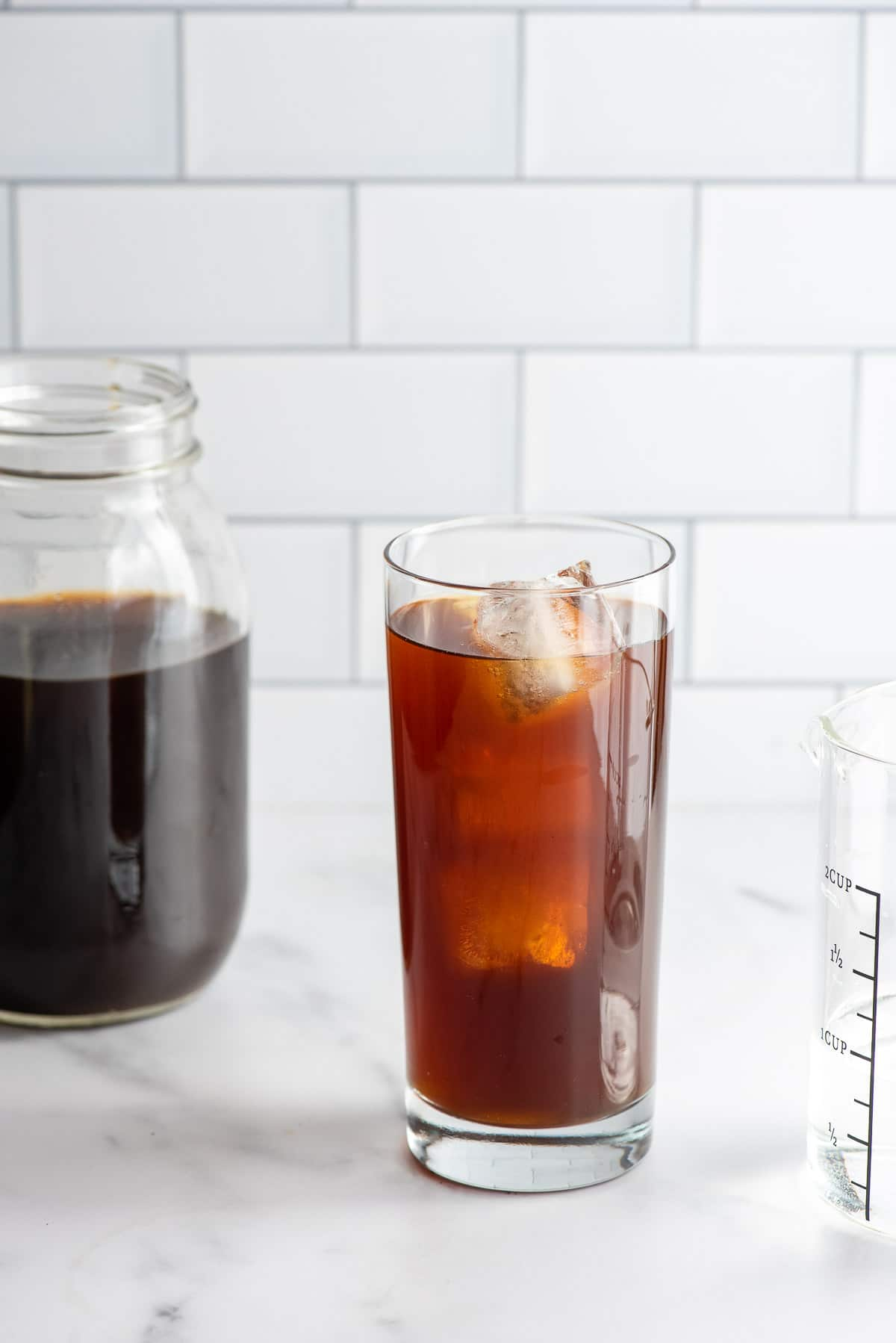 Cold Brew coffee concentrate and water in a tall glass with ice