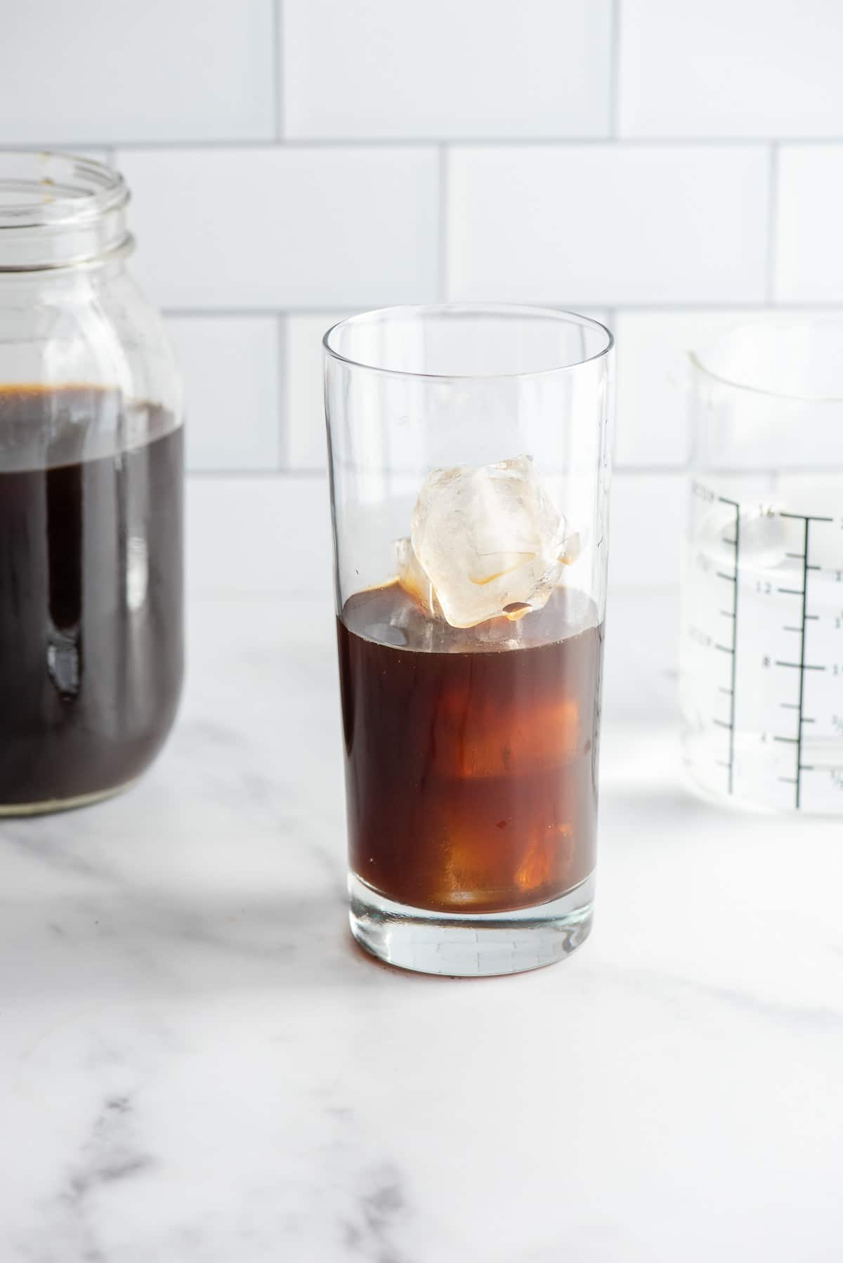 Making Cold Brew Coffee from homemade coffee concentrate in a glass with ice
