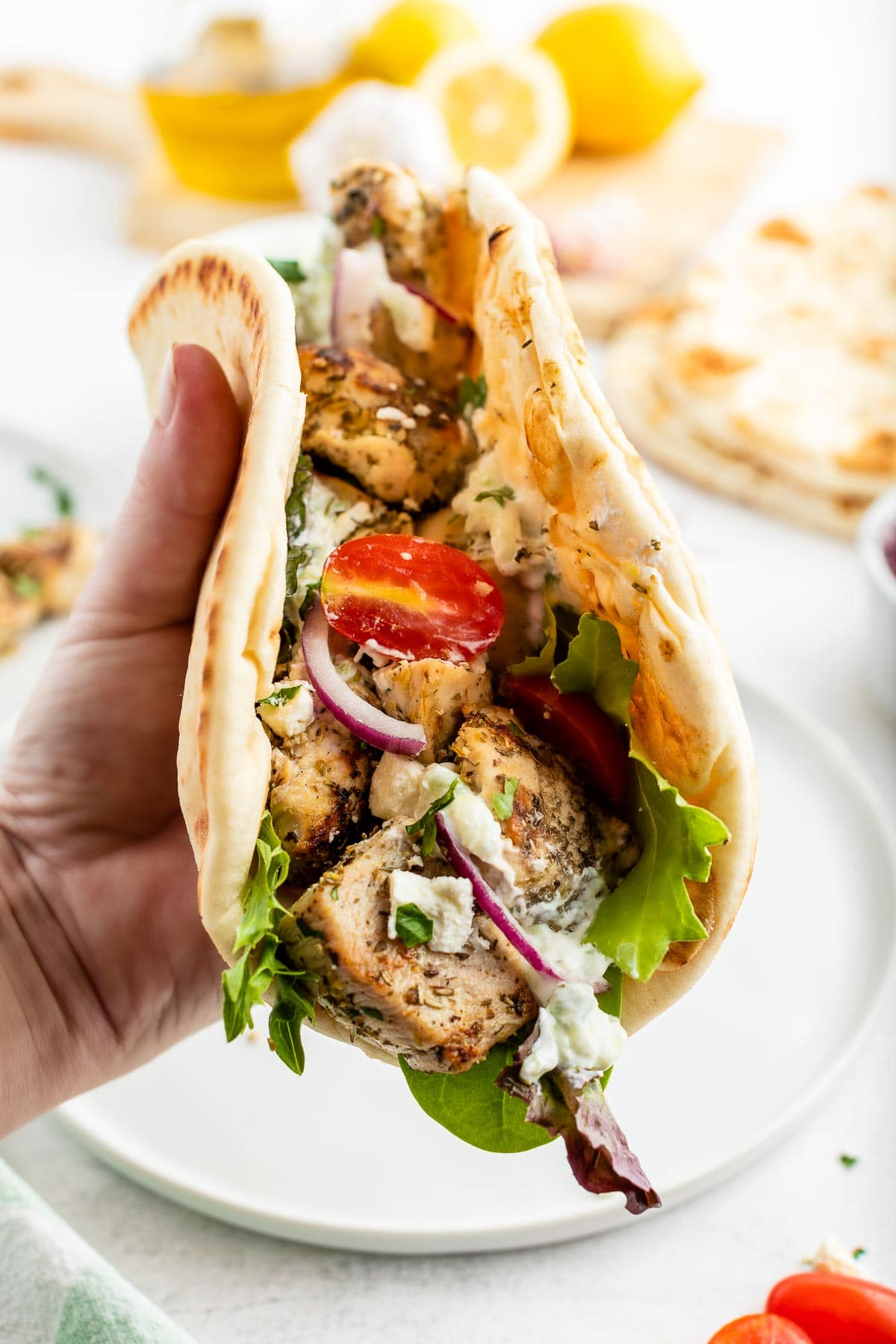hand holding a soft flatbread folded with chicken souvlaki, tomatoes, onions and feta cheese inside