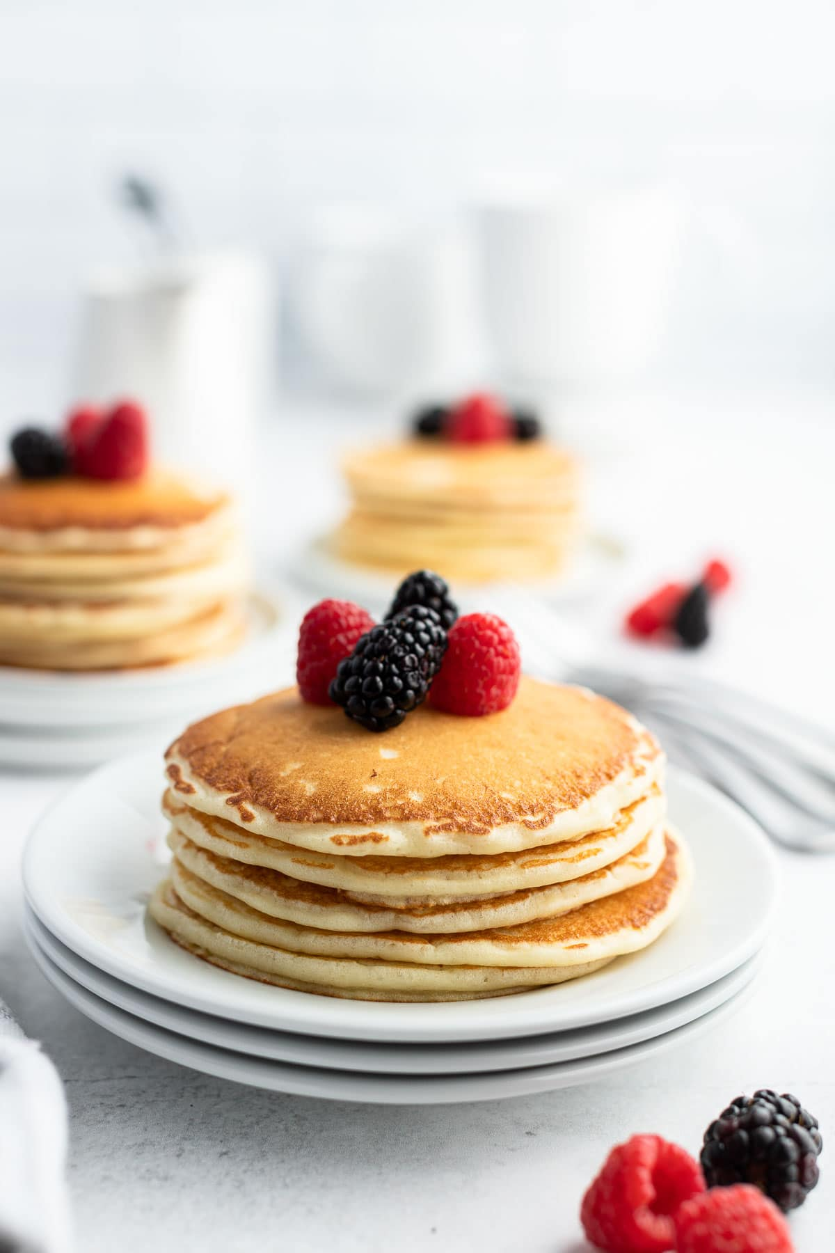 stack of buttermilk pancakes with berries on top