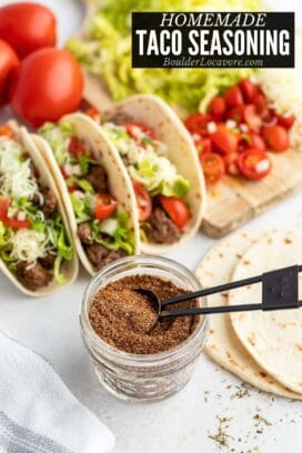 homemade taco seasoning in a small jar with tacos behind