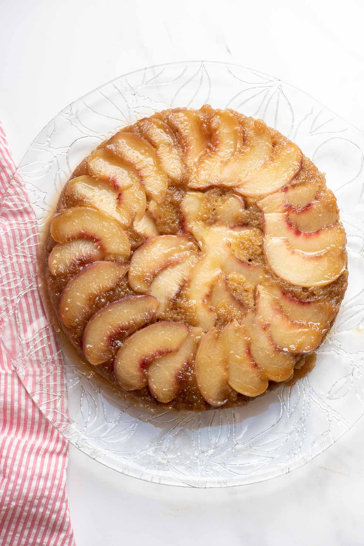 peach upside down cake on serving platter and cloth