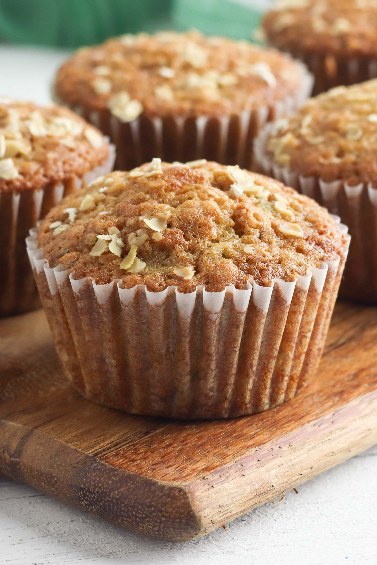 single zucchini muffin on wood cutting board