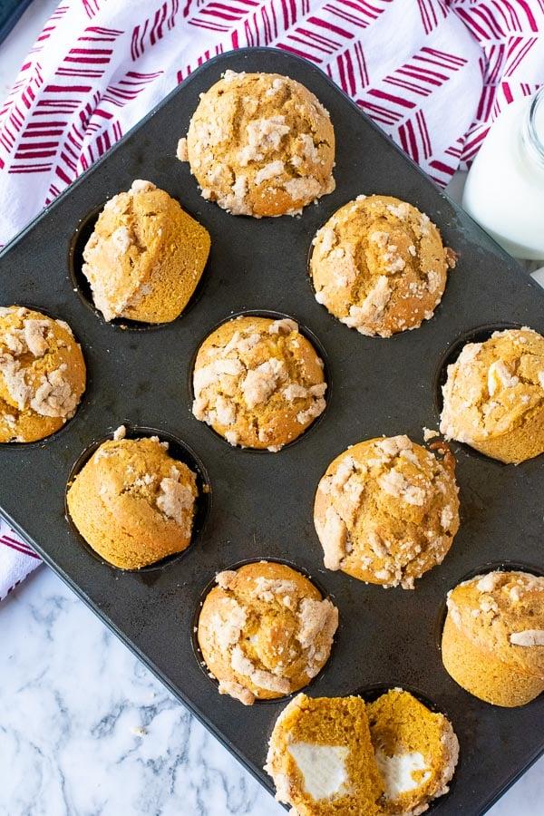 muffin pan of pumpkin cream cheese muffins