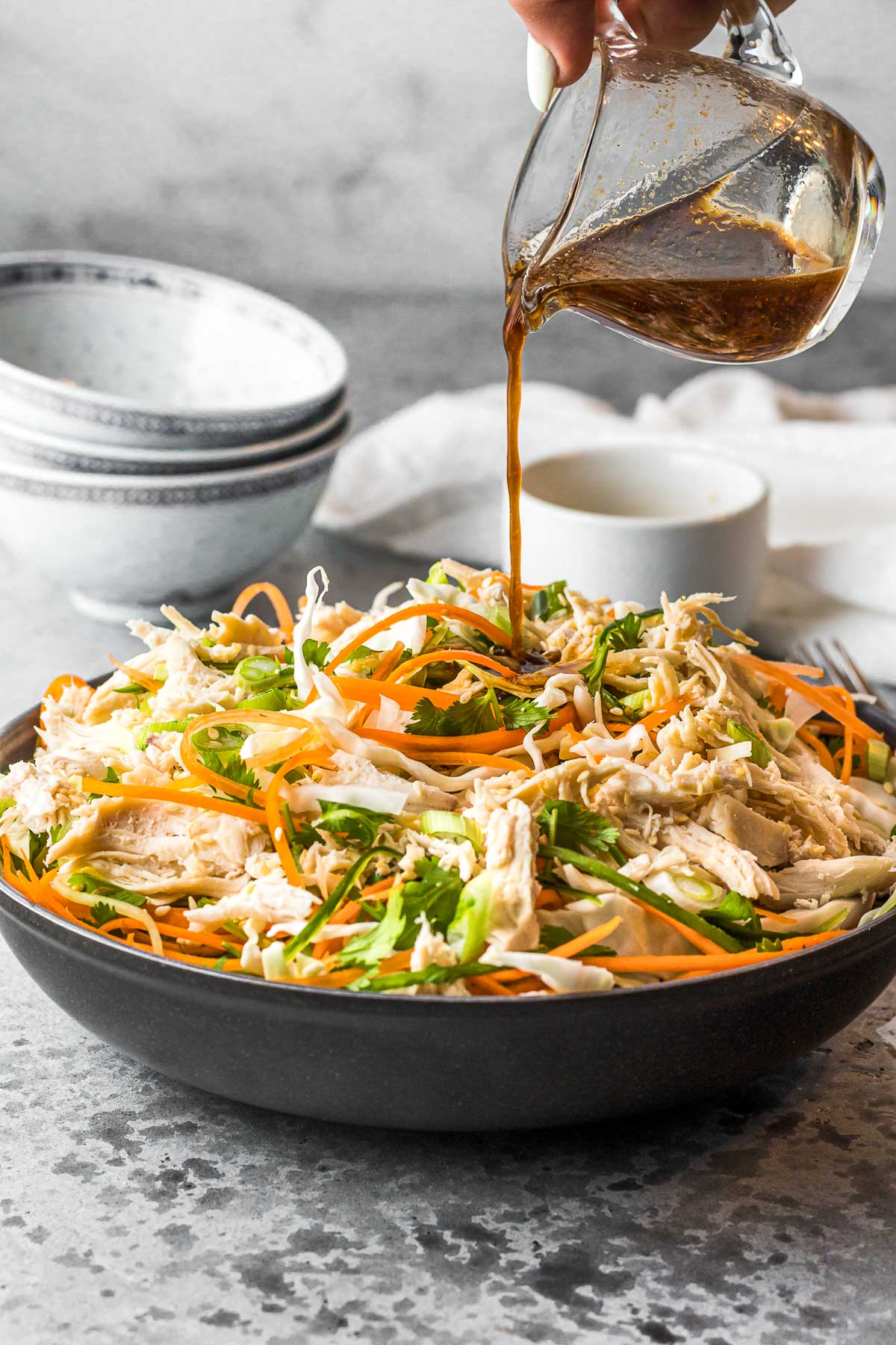 Asian Chicken Salad pouring dressing