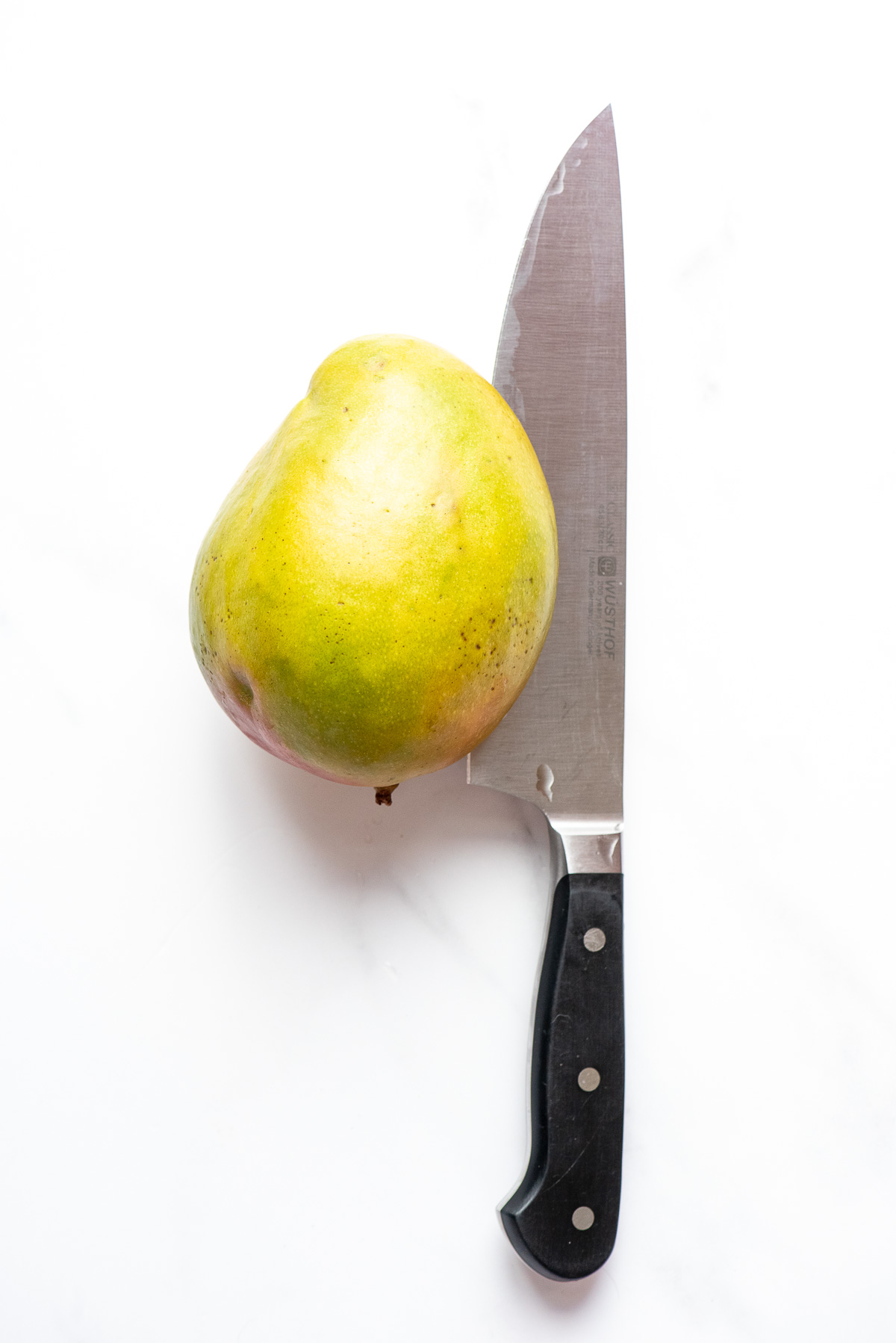 cutting through a mango with a large knife