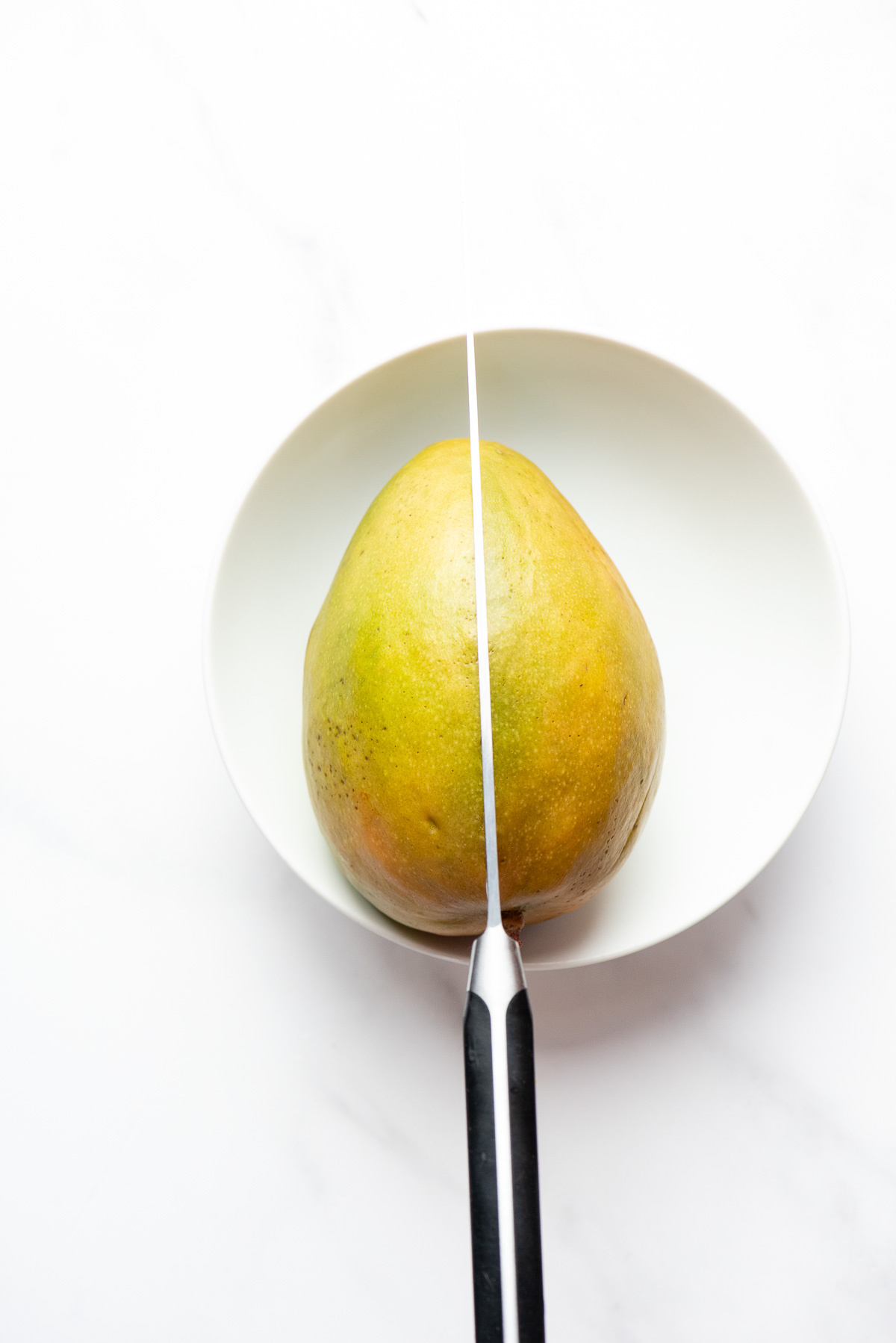 cutting a mango - knife in fruit