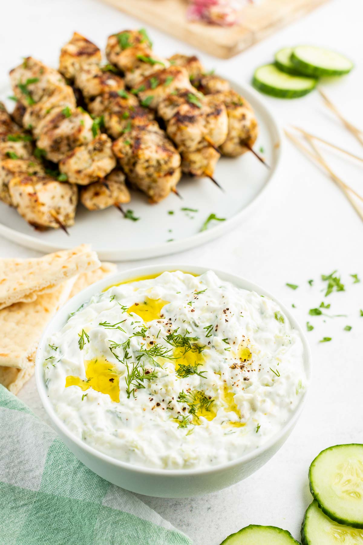 tzatziki sauce with chicken souvlaki skewers in the background