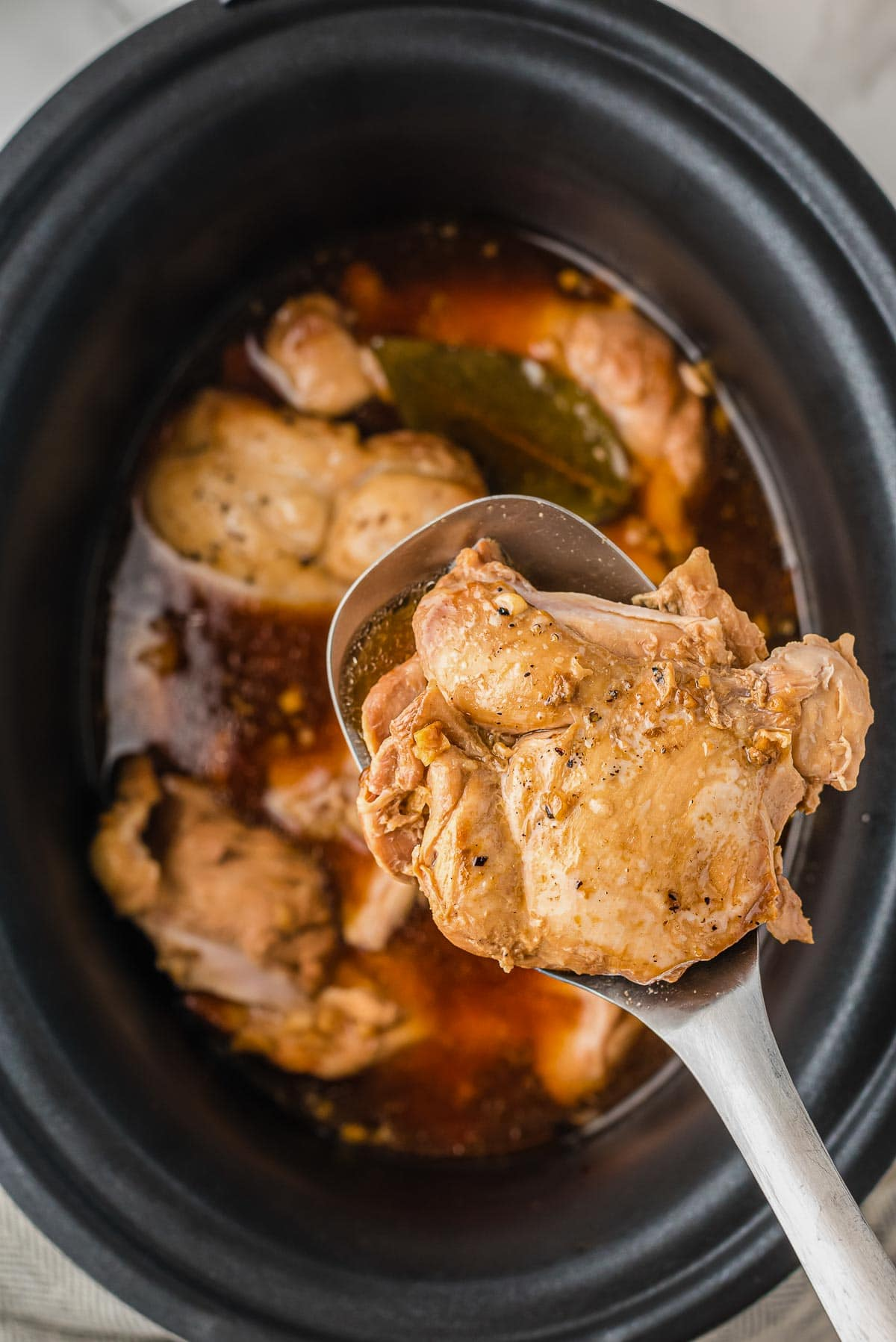 chicken adobo cooked in slow cooker on spoon