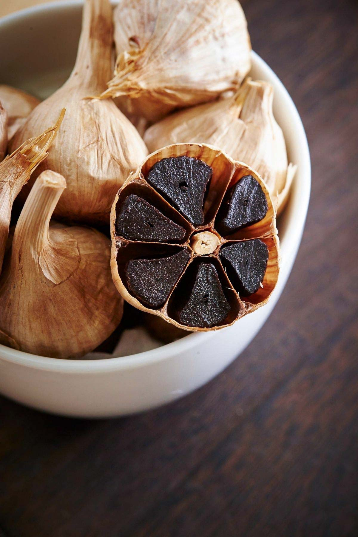 close up black garlic cloves in white bowl