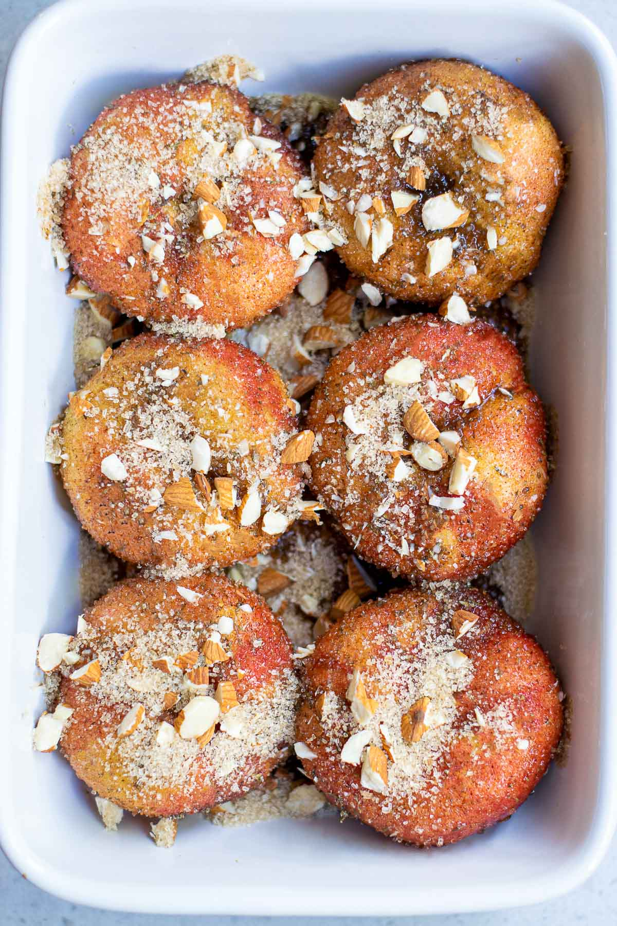 donut peaches in baking pan with nuts