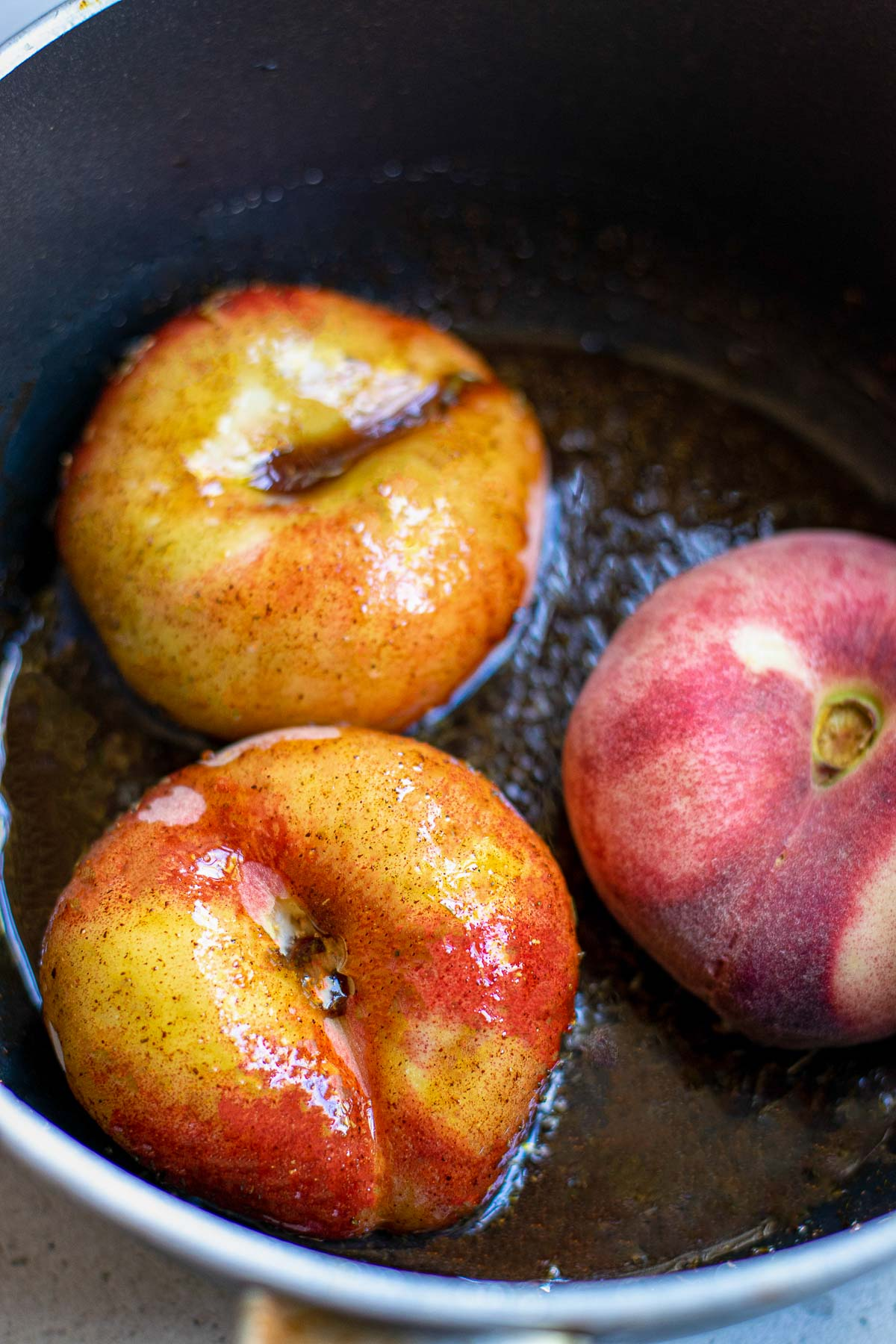 donut peaches in saucepan with sauce