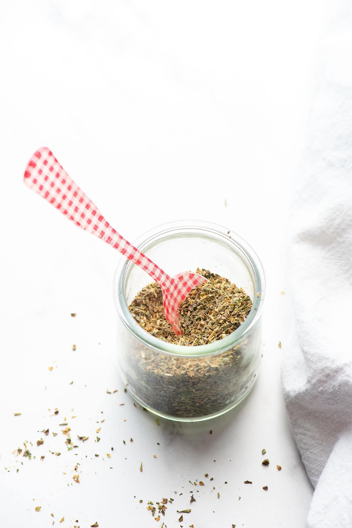 Italian seasoning in jar close up with spoon