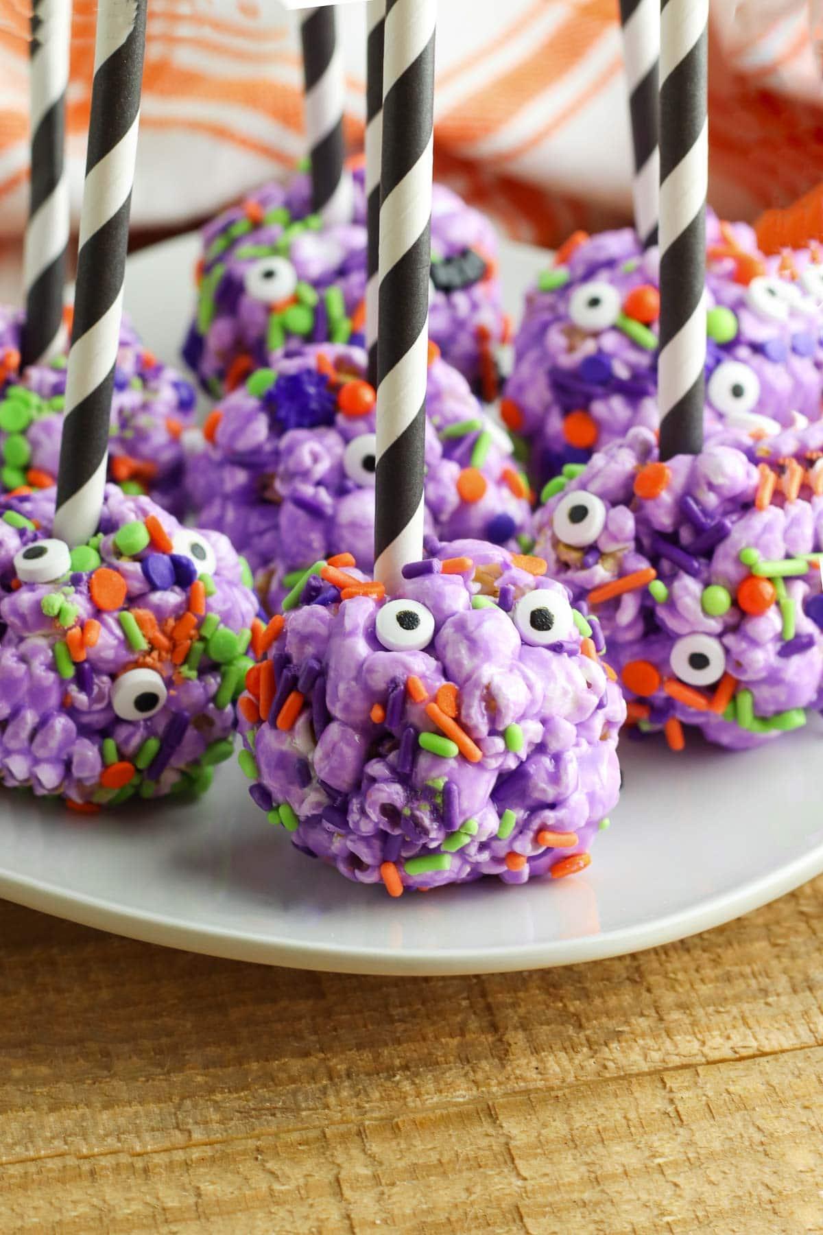 halloween popcorn balls with sticks on plate