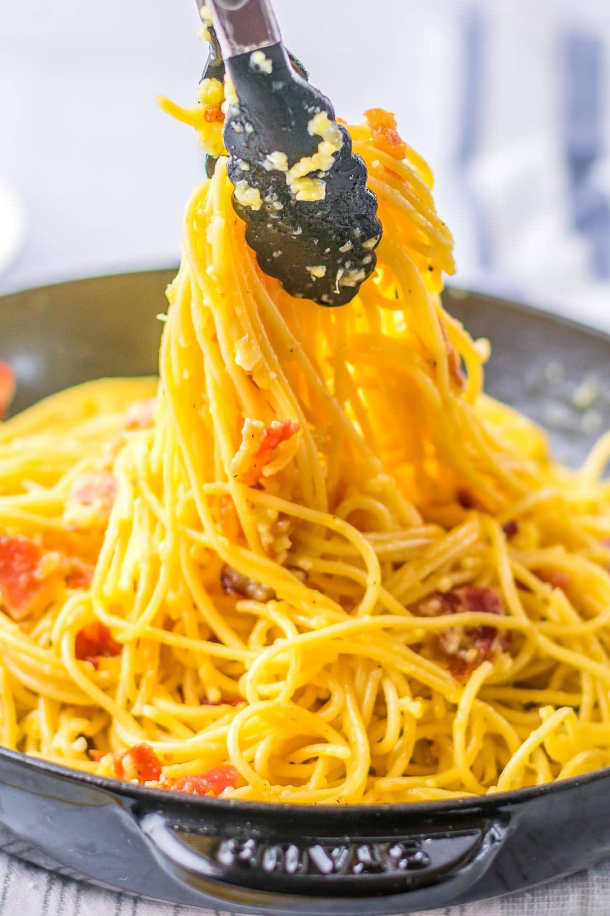 spaghetti carbonara with tongs