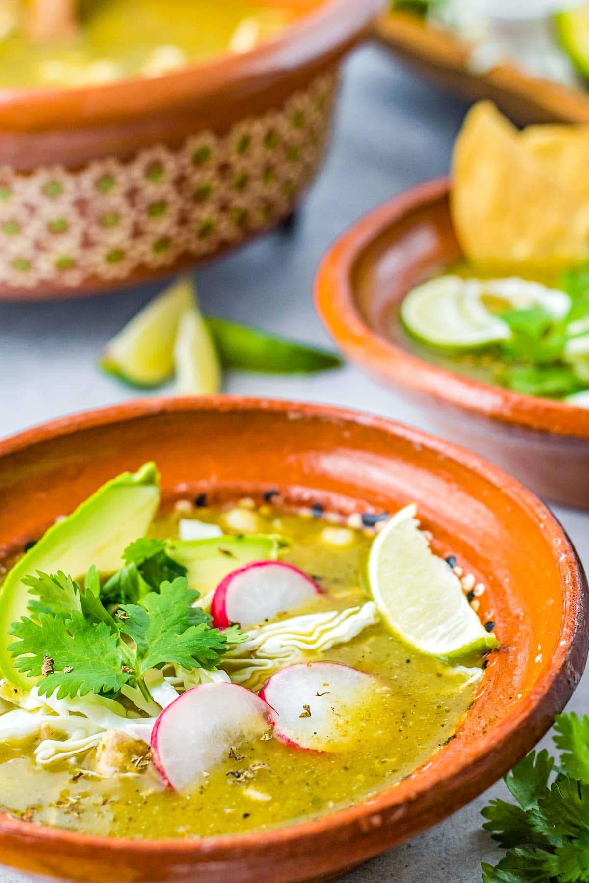 bowls of pozole verde with toppings