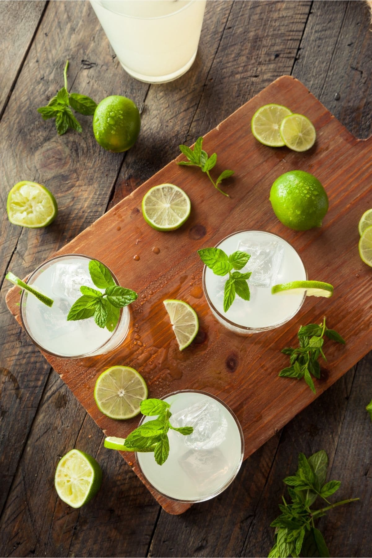GLASSES OF LIMEADE FROM OVERHEAD WITH LIMES