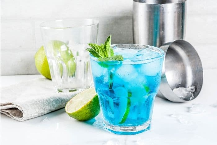 Blue Margarita in a glass with cocktail shaker