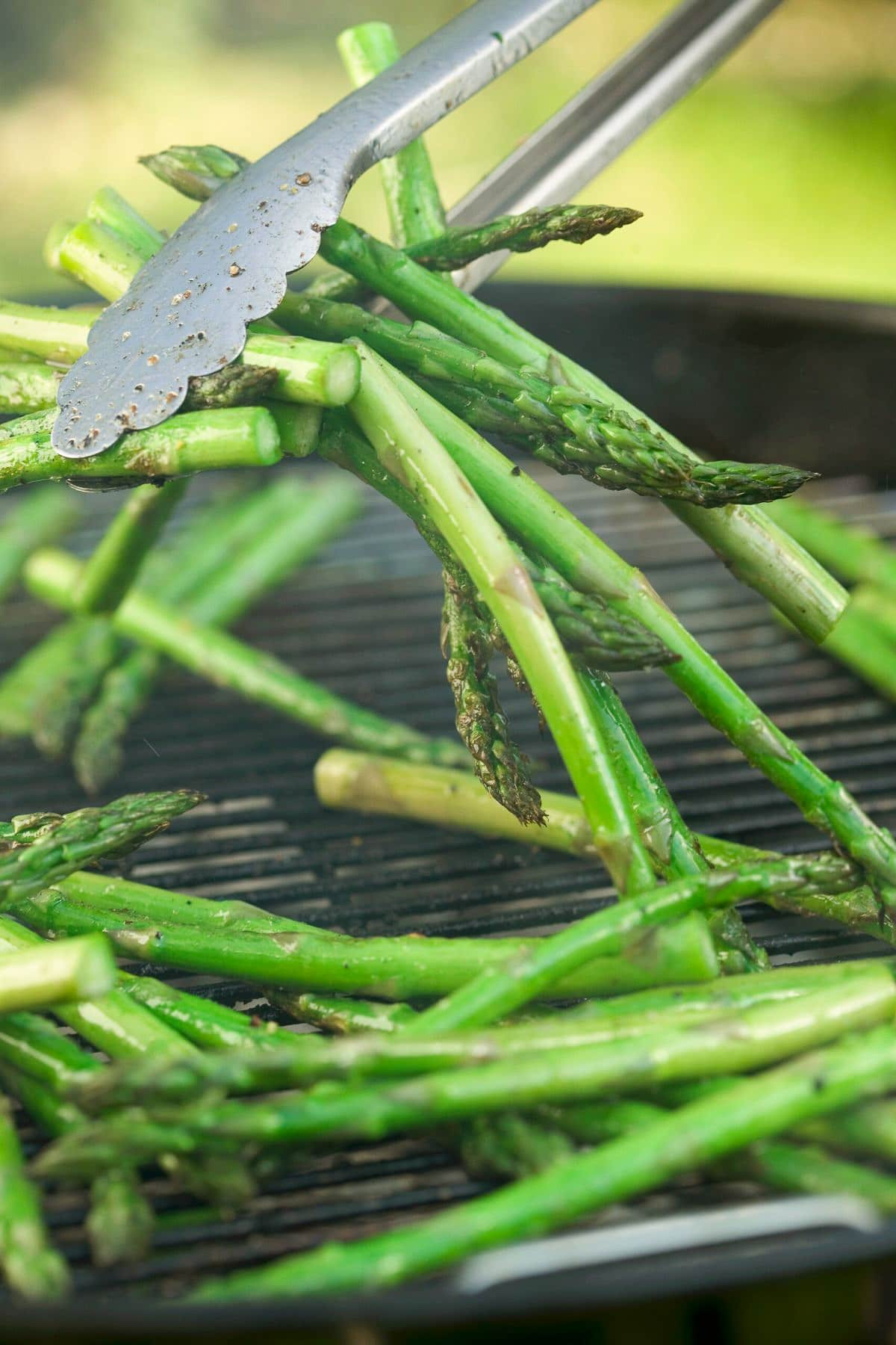 asparagus on grill being flipped by tongs