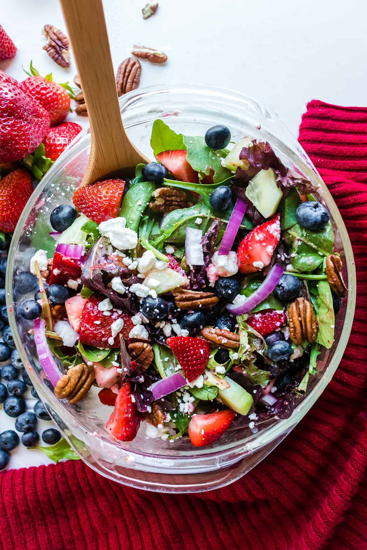 tossed strawberry salad with blueberries, goat cheese, red onions in a clear glass bowl