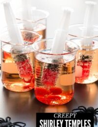 creepy Shirley Temple drinks for Halloween in beakers with syringes